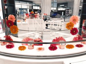 Clinique counter top with red, orange and pink daisies for moisture surge product launch